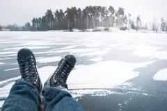 人在冬天滑冰一个透明的结冰的湖,洒与雪 库存照片