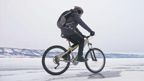 人在冰洞穴附近骑自行车 与冰洞和冰柱的岩石是非常美丽的 骑自行车者打扮 股票录像