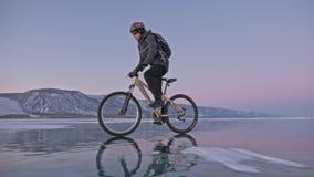 人在冰骑自行车 骑自行车者在灰色下来夹克、背包和盔甲打扮 冰冻 股票视频