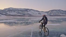 人在冰骑自行车 骑自行车者在灰色下来夹克、背包和盔甲打扮 冰冻 股票录像