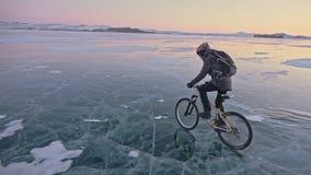 人在冰骑自行车 骑自行车者在灰色下来夹克、背包和盔甲打扮 冰冻 影视素材
