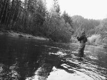 人在冷的冬天天气的用假蝇钓鱼 图库摄影