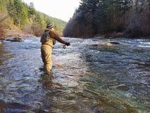人在冷的冬天天气的用假蝇钓鱼 库存图片