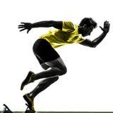 年轻人在出发台剪影的短跑选手赛跑者 免版税库存照片