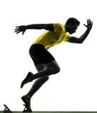 年轻人在出发台剪影的短跑选手赛跑者 免版税库存图片