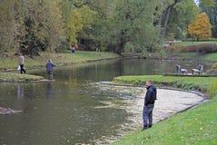 人在华沙城市池塘钓鱼 库存照片