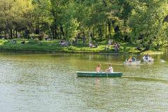 人在卡罗尔Park湖的小船乘驾在春日 免版税库存照片