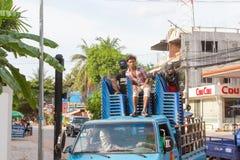 人在卡车背后乘坐在蓝色塑料椅子 免版税库存照片