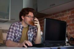 年轻人在厨房和饮用的茶里坐在一台膝上型计算机 库存照片