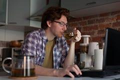 年轻人在厨房和饮用的茶里坐在一台膝上型计算机 免版税库存照片