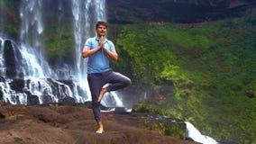 人在右腿站立由瀑布折叠在祷告的棕榈 影视素材
