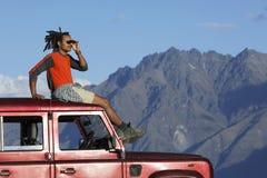 人在吉普顶部的阴影眼睛在山附近 免版税库存图片