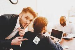 人在同事后面的被黏贴的贴纸在办公室 图库摄影