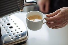 人在咖啡壶旁边拿着杯子浓咖啡 免版税库存图片