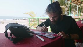 人在咖啡馆和印度食物的画的图象坐在写生簿的由艺术标志 影视素材