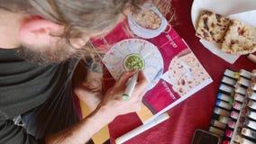 人在咖啡馆和印度食物的画的图象坐在写生簿的由艺术标志 股票视频