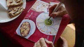 人在咖啡馆和印度食物的画的图象坐在写生簿的由艺术标志 股票录像