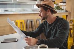 人在咖啡馆的读书菜单 免版税库存图片