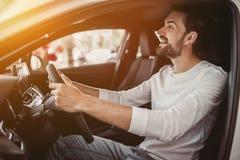 人在售车行中,坐在看在后视镜的汽车 免版税库存图片