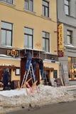 人在啤酒客栈垂悬一个标志在冬天 图库摄影