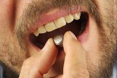 人在嘴投入电池,去吞下它,正面图 免版税库存照片