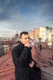 年轻人在圣彼德堡抽在屋顶的雪茄 免版税图库摄影