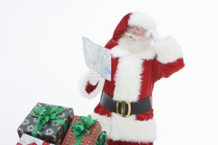 人在圣诞老人成套装备读书路线图 免版税库存照片