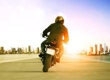 人在城市交通路的骑马摩托车背面图peo的 免版税库存照片
