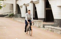 年轻人在城市街道上的骑马自行车 库存图片