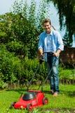 人在夏天割草坪 免版税库存照片