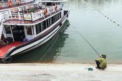 人在夏天在背景中坐和钓鱼在努力去做的游船附近哈隆海湾在广宁省,越南 免版税库存照片