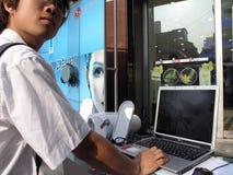 人在外部显示的尝试膝上型计算机在商店 免版税库存图片