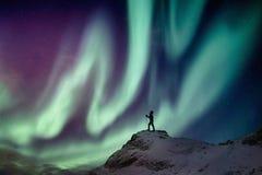 人在多雪的山峰的登山人身分与极光borealis和满天星斗 免版税库存图片