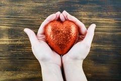 人在她的手上的拿着手工制造红色心脏 爱 2月14日 日s华伦泰 免版税图库摄影