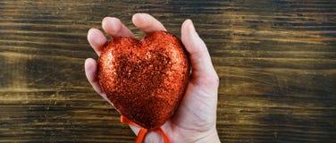 人在她的手上的拿着手工制造红色心脏 爱 2月14日 日s华伦泰 免版税库存照片