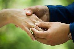 人在妇女上把定婚戒指放 免版税库存图片