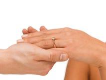 人在妇女手上把婚戒放 免版税图库摄影
