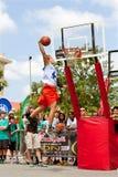 年轻人在室外灌篮比赛飞跃高 免版税库存照片