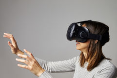 人在家坐佩带虚拟现实耳机的沙发 免版税图库摄影