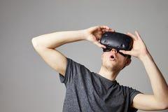 人在家坐佩带虚拟现实耳机的沙发 免版税库存图片