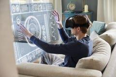 人在家坐佩带虚拟现实耳机的沙发 库存照片