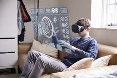 人在家坐佩带虚拟现实耳机的沙发 图库摄影