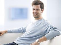 年轻人在家坐沙发 免版税库存照片