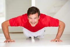 人在家庭体操方面的执行俯卧撑 免版税库存图片