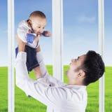 人在家拿着一个可爱的男婴 库存照片