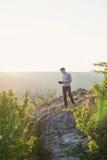 人在小山和读站立书垂直 图库摄影