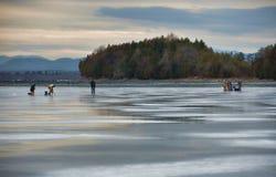 人在尚普兰湖的冰渔黄昏的 免版税库存图片