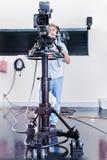 人在屋子里操作一台巨大的演播室照相机 免版税库存照片