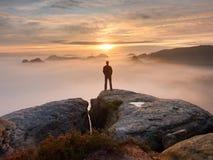 人在岩石峰顶单独站立  观看对秋天太阳的远足者在天际 免版税图库摄影