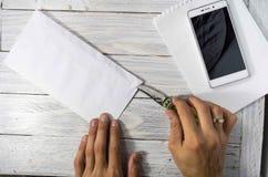 人在工作场所打开与一把刀子的信封 免版税库存照片